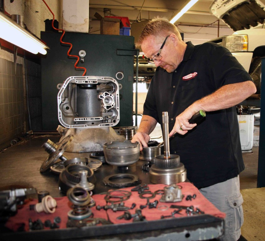 Photo of Michael, owner and transmission specialist at our shop, working on auto parts